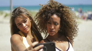 Confident grimacing women having fun while taking selfie and grimacing at camera on background of shoreline of ocean.