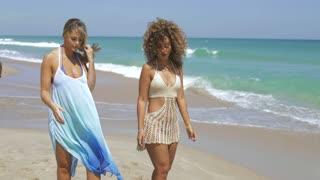 Confident multiethnic women in beachwear strolling on seaside relaxing in sunlight and speaking calmly.
