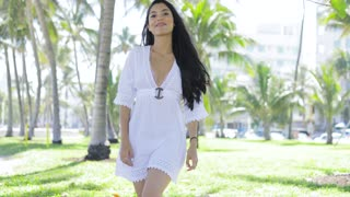 Confident pretty woman with long black hair wearing white beachwear and walking in green tropical park looking at camera.