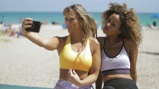 Confident sportive women using smartphone on tropical coastline and taking selfie in bright sunshine having fun.