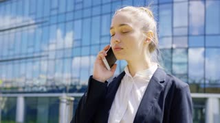 Confident young woman in formal clothing talking smartphone while looking away on background of city.
