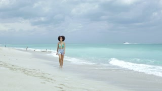 Content black woman in bikini top and shorts running happily on sandy beach laughing at camera on background of clouds.