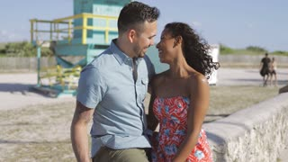 Content black woman in dress embracing with smiling man sitting on stone fence on waterfront and laughing in love.
