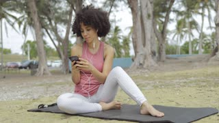 Content fit black woman listening to music with headphones and surfing phone while sitting on mat in park.