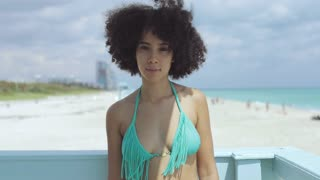 Content pretty African-American girl in bikini top standing in sunshine on beach looking at camera with smile.
