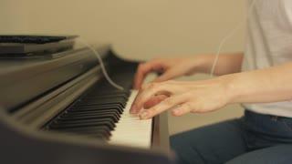 Crop close-up woman hands playing digital piano.