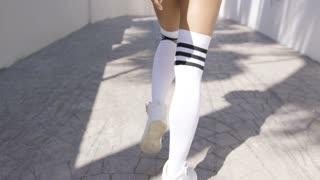 Crop photo of female wearing sportive knee-high socks walking on footway, bottom part.
