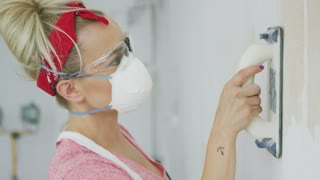 Crop side view of blond female in red headband and protective mask and glasses concentrating on grinding white plastered wall with sandpaper tool