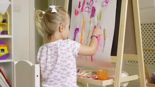 Cute creative little girl artist painting at an easel sitting applying brightly colored paints in an abstract design