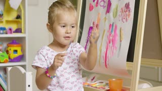 Cute little girl artist creating a colorful abstract painting on a sheet of paper attached to a blackboard in her playroom at home dabbing paint on her hand for a palm print.