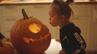 Cute little girl in Halloween costume standing near table and trying to puff out candle in scary jack-o-lantern.