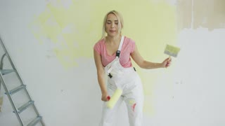 Doing repairs at home happy young blond female in white overalls holding roller and brush covered in yellow paint dancing at half-painted wall with open mouth.