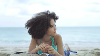 Dreaming young black girl in beachwear lying on towel on sandy shoreline looking away in contemplation.