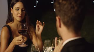 Elegant young woman chatting with her date during a romantic meal at a nightclub or restaurant smiling as she holds a glass of red wine