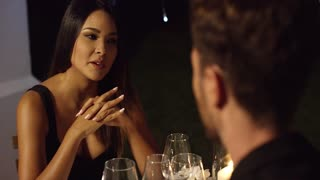 Elegant young woman enjoying a dinner date talking to a young man opposite her at the restaurant table gesturing with her hands