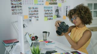 Elegant young woman in glasses working as creative designer in office and watching photos on camera sitting at table.
