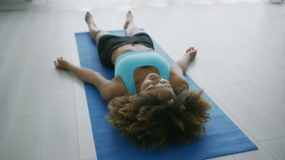 Ethnic curly woman in sportswear lying on mat at home and stretching hands looking peaceful and calm while practicing meditation.