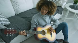 Ethnic young model wearing stylish sweater playing guitar while lounging on floor of living room at home looking content.