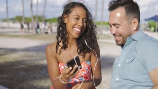Excited laughing man and black girl listening to music and sharing smartphone while sitting on seafront in sunlight.