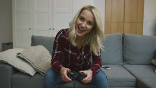 Excited young woman in checkered shirt holding controller and playing video game while sitting on comfortable sofa.