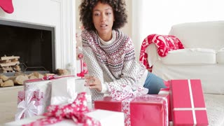 Excited young woman unwrapping her Christmas gifts sitting on the floor surrounded by a pile of gift wrapped boxes selecting one with a smile