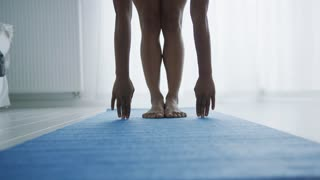 Faceless shot of anonymous woman bending forward while stretching body and training yoga on mat home in morning time.