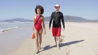 Female and male lifeguards walking along beach with orange rescue float. Tarifa beach. Provincia Cadiz. Spain.