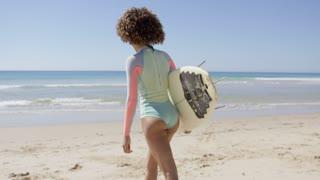 Female holding surfboard walking into sea to surf, back view. Tarifa beach. Provincia Cadiz. Spain.