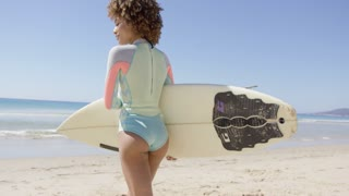Female holding white surfboard walking to sea to surf. Back view. Tarifa beach. Provincia Cadiz. Spain.