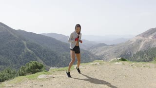 Female in sportswear and red boxing wraps kicking with leg up and looking at camera against mountains.