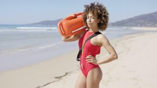 Female lifeguard wearing red swimsuit posing with rescue float on beach. Tarifa beach. Provincia Cadiz. Spain.