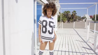 Female posing raising t-shirt, wearing sportive outfit, white knee-high socks, looking down.