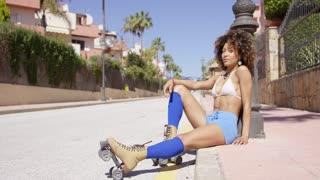 Female wearing blue shorts and knee-high socks sitting on sidewalk wearing roller skates looking at camera.