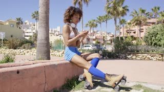 Female wearing rollerskates and swimsuit top with shorts sitting on curb with headphones on her neck