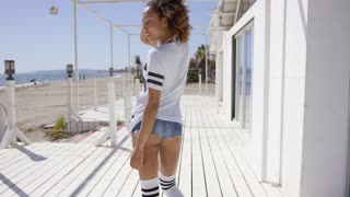 Female wearing sportive knee-high socks and t-shirt looking back over her shoulder on beach background.