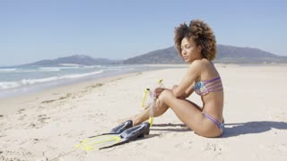 Female wearing two-piece swimsuit sitting on beach with flippers and mask. Tarifa beach. Provincia Cadiz. Spain.