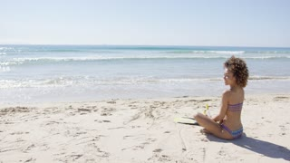 Female wearing two-piece swimsuit sitting with arms outstretched to sides on beach. Tarifa beach. Provincia Cadiz. Spain.