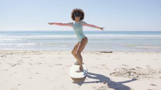 Female wearing virtual reality glasses standing on surfboard on sea background, Tarifa beach. Provincia Cadiz. Spain.