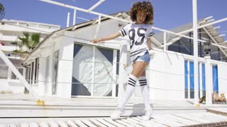 Female wearing white sportive knee-high socks and t-shirt standing leaning on fencing on white beach houses background.