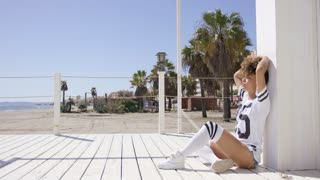 Female wearing white sportive t-shirt and knee-high socks sitting on floor on beach and palm trees background.