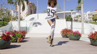Female wearing white t-shirt and knee-high, roller skates posing on white building background.