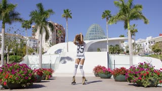 Female wearing white t-shirt and knee-high socks riding on roller skates in park with palm trees.