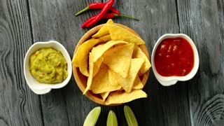 Flat lay of bowl with corn nacho chips served on wooden table with different sauces and chili pepper