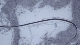 From above aerial shot of picturesque white lands of woods with snow covering ground in gloomy weather, Poland.