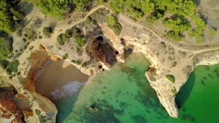 From above aerial view of rough cliffs on shoreline of tropical ocean with green water washing white sands in lagoon, Portugal, Algarve.
