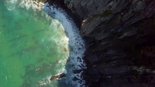 From above aerial view of turquoise ocean waves splashing against coast cliffs making white foam under bright sunlight in Algarve, Portugal.