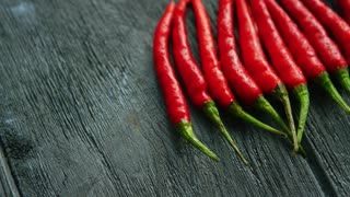 From above shot of layout of bright ripe red chili peppers arranged in row on rough wooden table