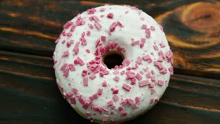 From above shot of round doughnut glazed with white icing and topped with pink sprinkles lying on wooden table