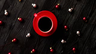 From above shot of tiny Christmas beads lying on dark wooden tabletop around cup of aromatic hot beverage