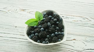 From above shot of white heart-shaped bowl filled with ripe blackberries and blueberries and mint leaves on wooden table